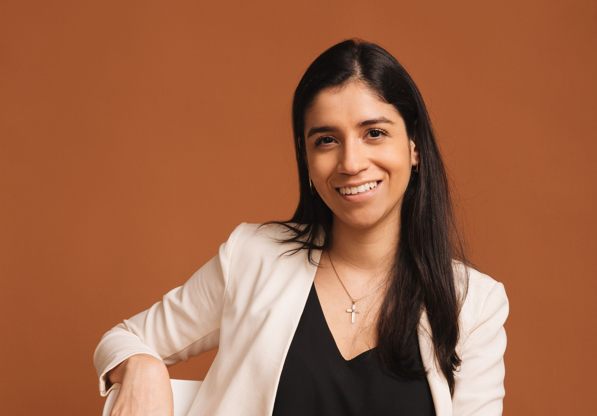 Portrait of a smiling Latina woman in a black shirt and cream blazer, sitting on a chair.